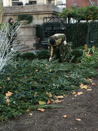 Workmen in Bryant Park add greenery to the landscape.