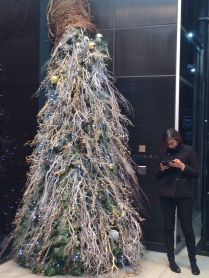 A passerby checks her phone while standing by a twiggy, silver and white tree.