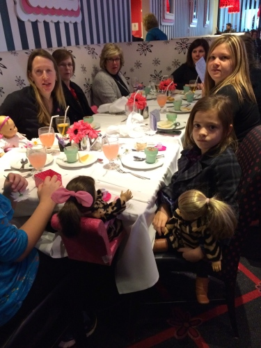 Moms, daughters, and dolls (see them in their special chairs attached to the table?) wait to be served at American Girl NYC.