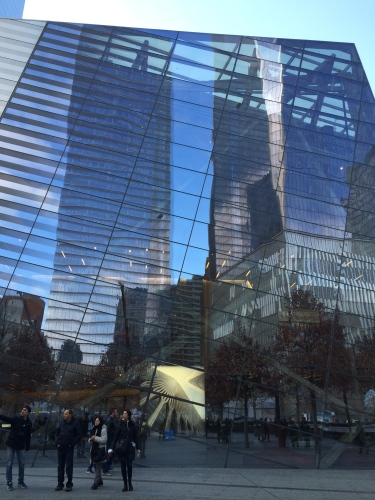 Tall monoliths reflected in a steel and glass wall outside the 9/11 Memorial Museum.