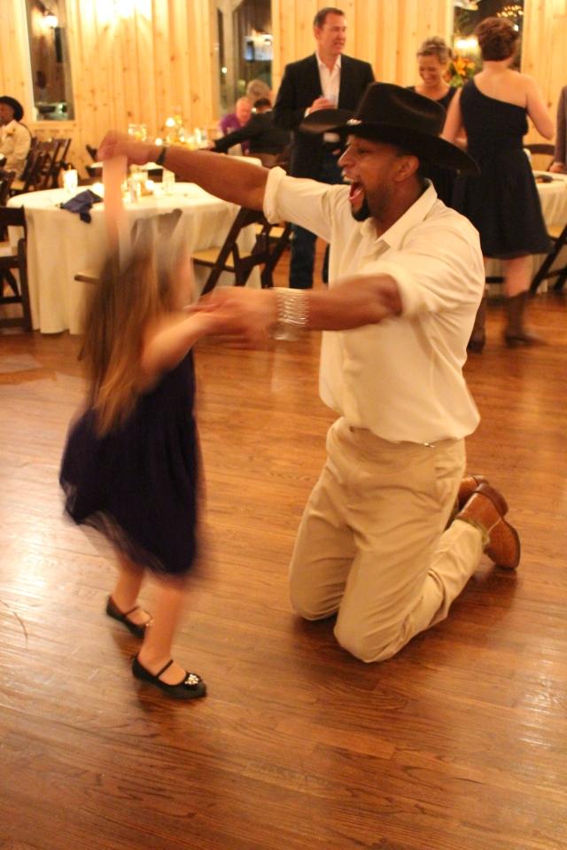 Groom dancing with little girl