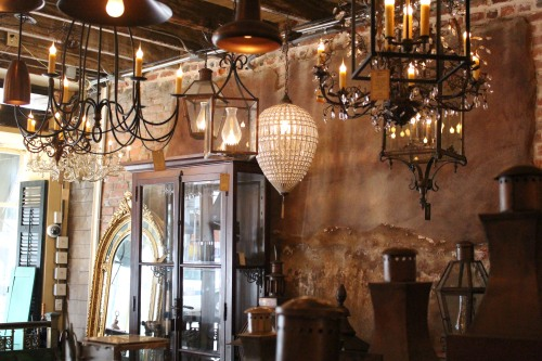 New lamps and mirrors contrast nicely with aged brick and peeling plaster walls.