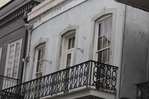 Two windows, one door open onto a stately ironwork balcony.