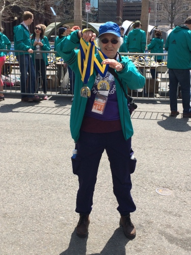 A volunteer shows off the Boston Marathon 2016 medals to spectators at the Finish Line.