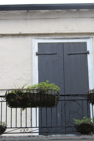 Painted black shutters form a backdrop for this monogrammed ironwork and hanging basket.