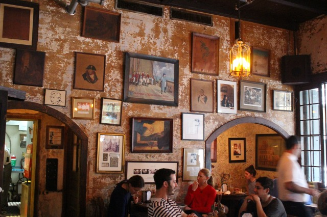 Old photos and memorabilia hang on an untouched wall at Napoleon House, New Orleans French Quarter.