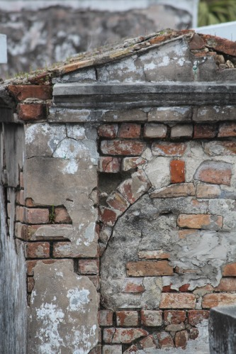 Exposed brick and plaster on this tomb with evidence of an arched cavity