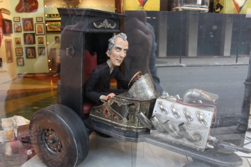 As seen in a window in French Quarter, artwork resembling a hearse with driver.