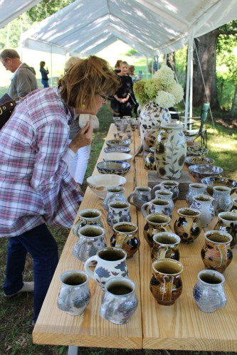 Under the tent: Looking over the selection of Michael Kline pottery.