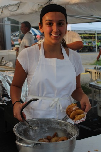 Smiling while serving -- this young lady worked fast to get hot doughnuts to hungry fairgoers.