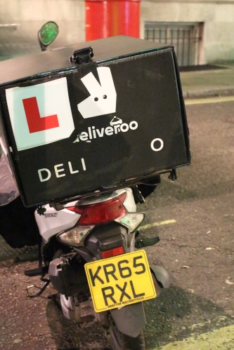 A Deliveroo box sits empty on the back of a bike -- parked while the driver makes a delivery.