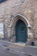 Stone home with arched doorway and alcove for boots? at bottom.