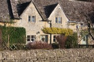 Lovely home in the Cotswolds decorated with a single wreath. But what stands out are the other elements -- stone fencing, interesting roofline, climbing vines, and tiled roof.