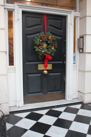 Checkerboard doorstep leads to this elegant door with central knob