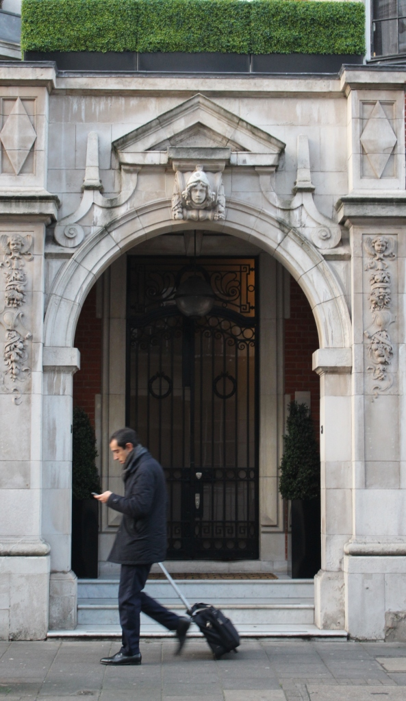 A passerby checks his phone in front of an elegant London doorway.