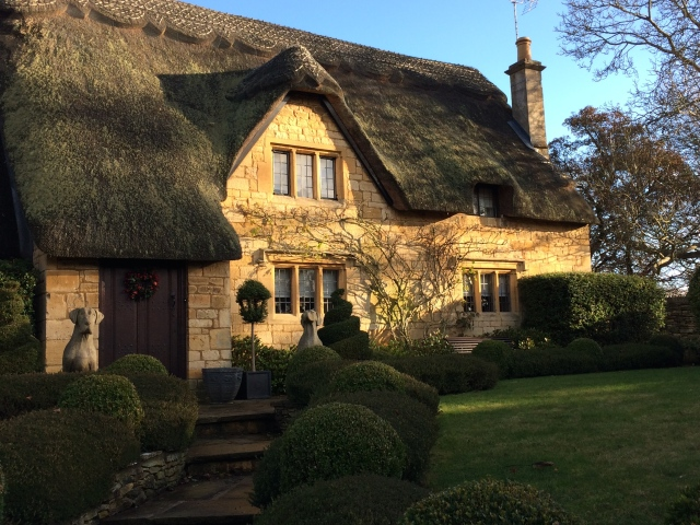 A storybook cottage with thatched roof in The Cotswolds, England.