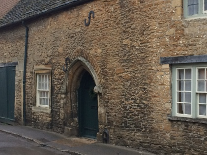 An arched door and large S bolts in old stone exterior
