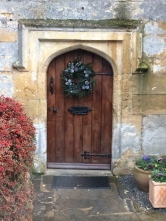 A Cotsolds wooden door with original hardware contrasting with cream exterior
