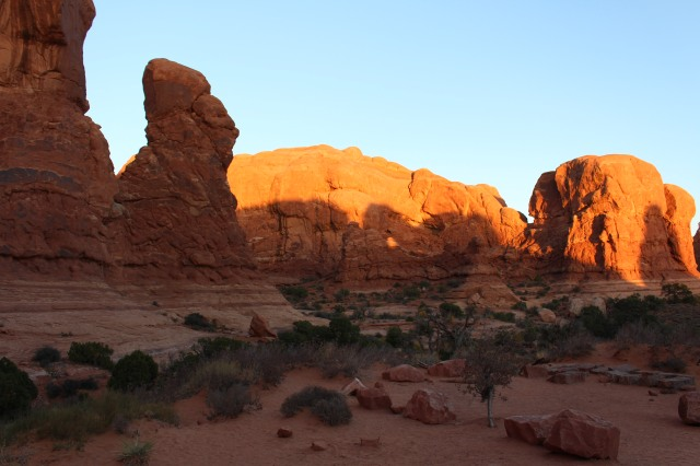 View from the parking lot at Double Arch: structures lit up by afternoon sun at Arches National Park