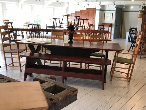 A light-filled showroom filled with custom tables, chairs, and stools of varying heights at Windsor Chairmakers