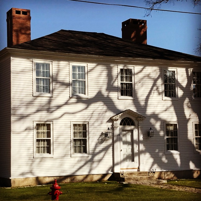 A stately Colonial almost looks spooky with early morning shadows racing across the facade.