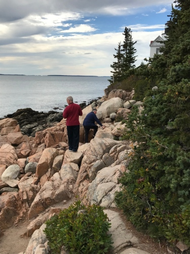 People climbing -- cautiously -- among the rocks, trying to get that perfect shot of Bass Harbor Light.