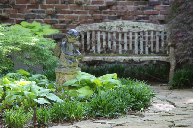 A weathered garden bench invites visitors to sit a spell and enjoy the quiet.