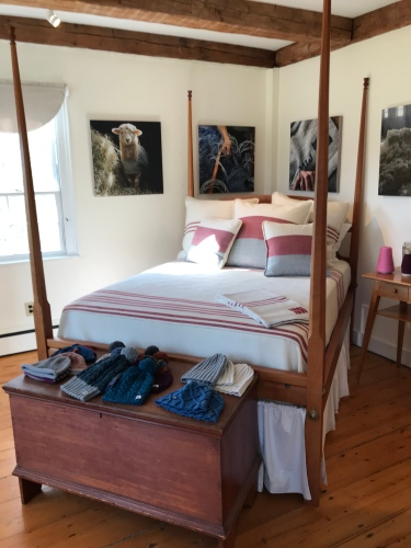 Simple white walls and a Shaker bed form the backdrop for goods made at Swans Island Blankets