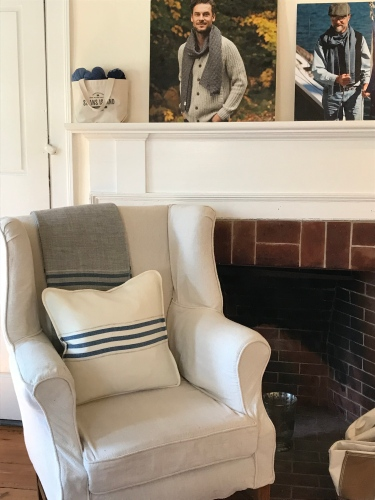 A simple white chair pulled up by the fireplace holds one of the striped, handwoven pillows from Swans Island Blankets.