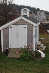 Sweet shed near the dock with pink flowers still in bloom.