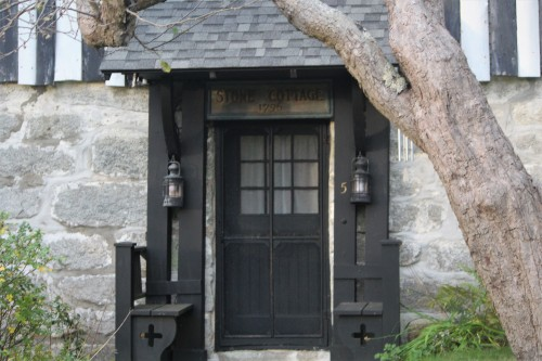 An inset door flanked by shutters and benches on the oldest cottage in Castine.
