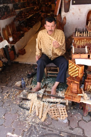 Whittling with his feet in an old, traditional way.