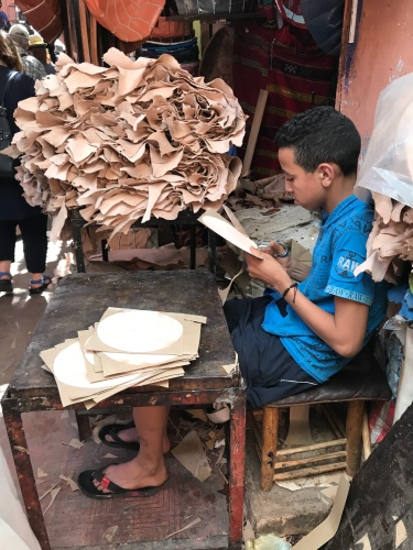 This young boy helps his father make leather poufs by cutting out the circles for the bottoms.