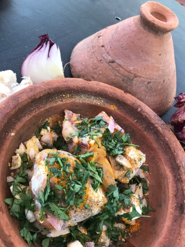 Layers of chopped onion, seasoned chicken and spices in a pottery tagine.
