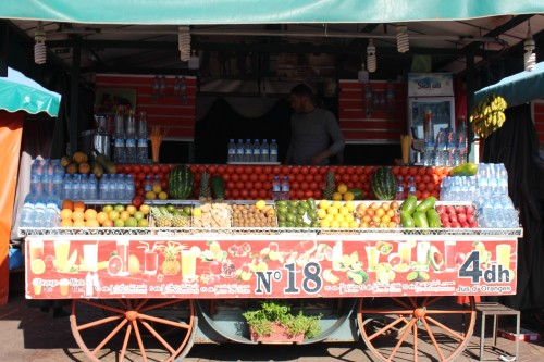 Fruit stall No. 18 with tidy rows of bottled water, oranges and other tropical fruits.