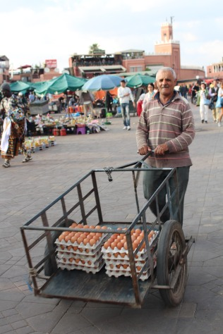 An egg salesman moves past other stalls making deliveries