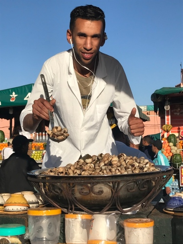 A seller of snails ready to scoop up a ladle full for you.