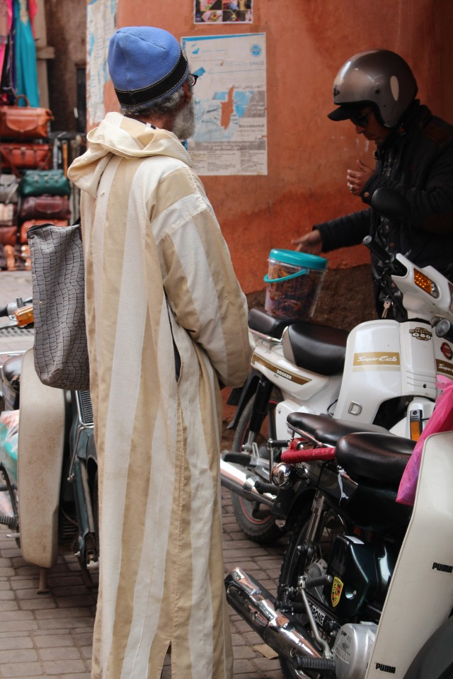 Old meets new as a man in traditional Moroccan dress chats with a friend in motorcycle attire.
