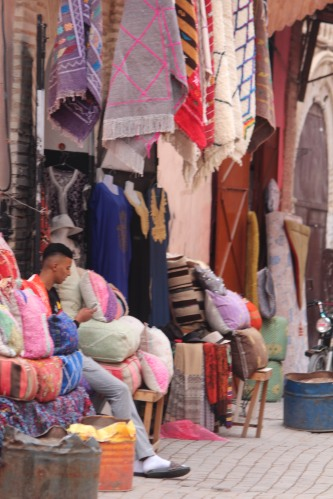 Rugs hang near the doorway of a shop in the Marrakech medina.