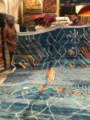 Salesmen unfurl rugs with contemporary colors and designs.