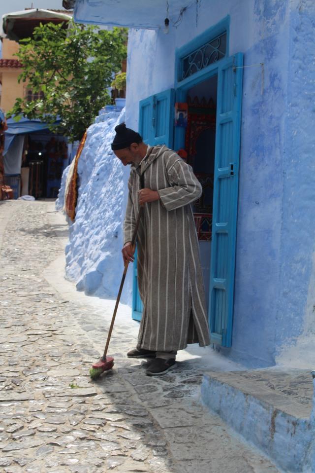 A man in Chefchaouen sweeps off the walkway in front of his door.