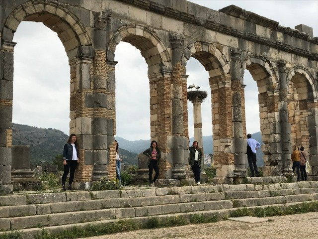 Some posing for pictures, some staring at storks at the archway in Volubilis