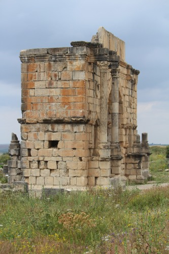 Remains of the Arch of Caracalla at Volubilis stand tall against the sky.
