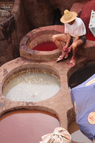 A worker rests on the side of dye pit in Fez.