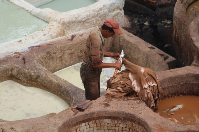 Worker in white pits of Fez tannery.